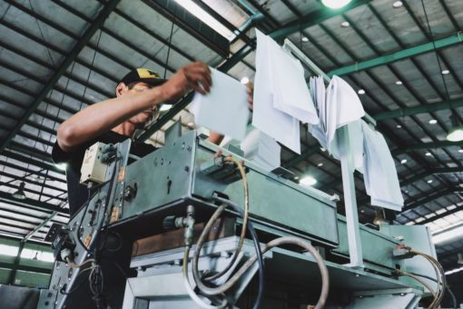 Holding bunch of white papers while operating large gray industrial machine